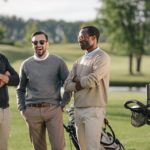 happy multiethnic golfers spending time together in golf course